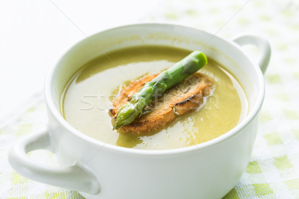 Asparagus soup in a white bowl with slice of bread and asparagus Stock photo © rafalstachura