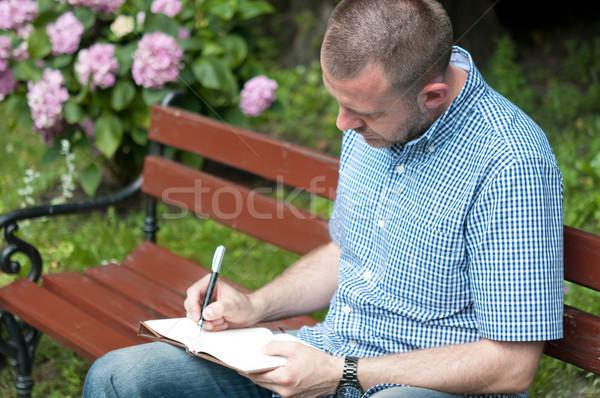 Homme écrit notepad jeune homme parc lumière Photo stock © rafalstachura