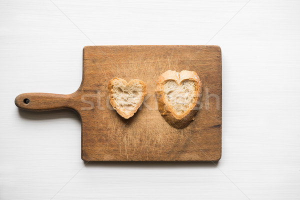 Heart-shaped slices of bread on old cutting board love concept Stock photo © rafalstachura