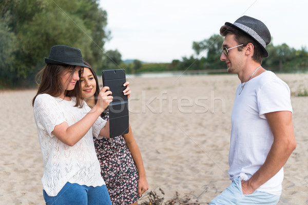 Young Adults Taking Pictures And Selfies On Sandy Beach Stock photo © rafalstachura