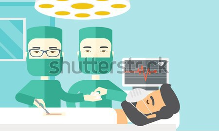 Stock photo: Two surgeons looking over a patient in an operating room