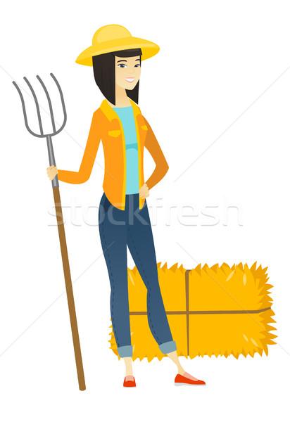 Young asian farmer holding a pitchfork. Stock photo © RAStudio