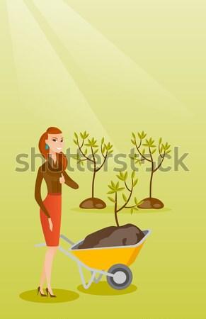 Vrouw voortvarend kruiwagen plant kaukasisch vrouwelijke Stockfoto © RAStudio