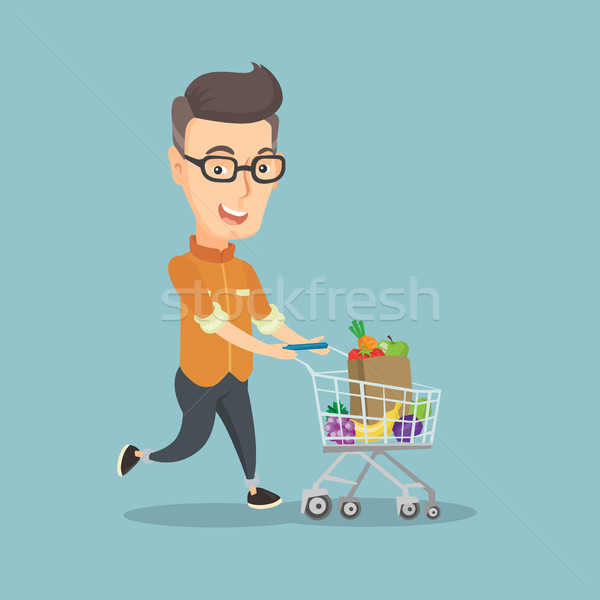 Man running with a trolley full of purchases. Stock photo © RAStudio