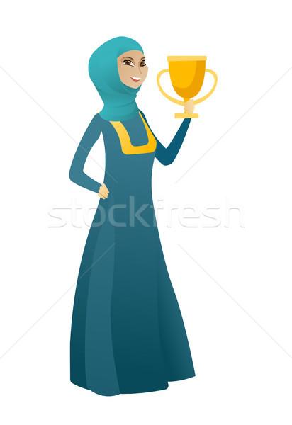 Muslim business woman holding a trophy. Stock photo © RAStudio