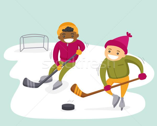 Multiethnic boys playing hockey on outdoor rink. Stock photo © RAStudio