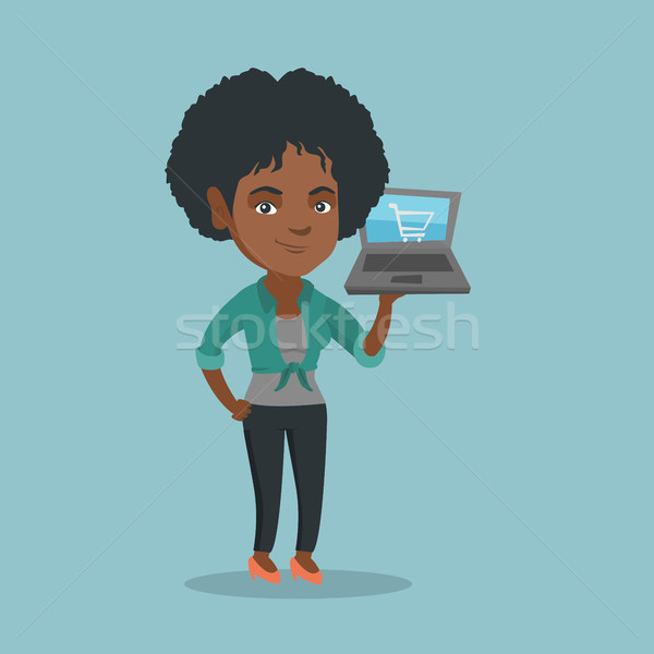 Woman holding laptop with shopping cart on screen. Stock photo © RAStudio