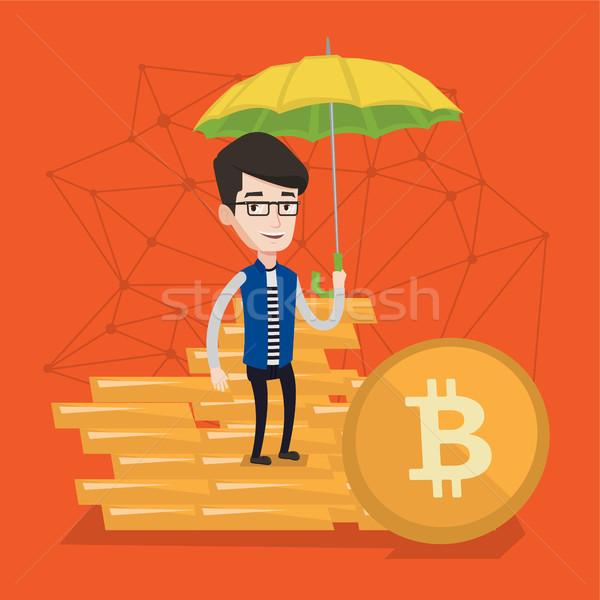 Young man with umbrella protecting bitcoin coins. Stock photo © RAStudio