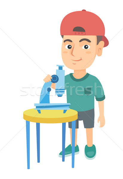 Little caucasian schoolboy using a microscope. Stock photo © RAStudio