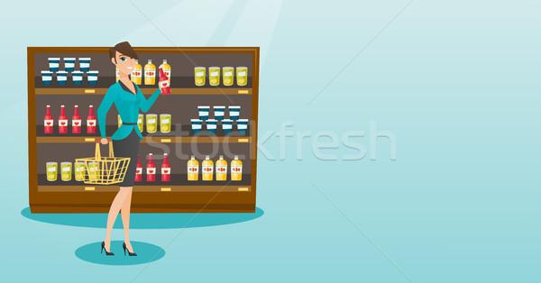 Woman holding shopping basket and bottle of sauce. Stock photo © RAStudio