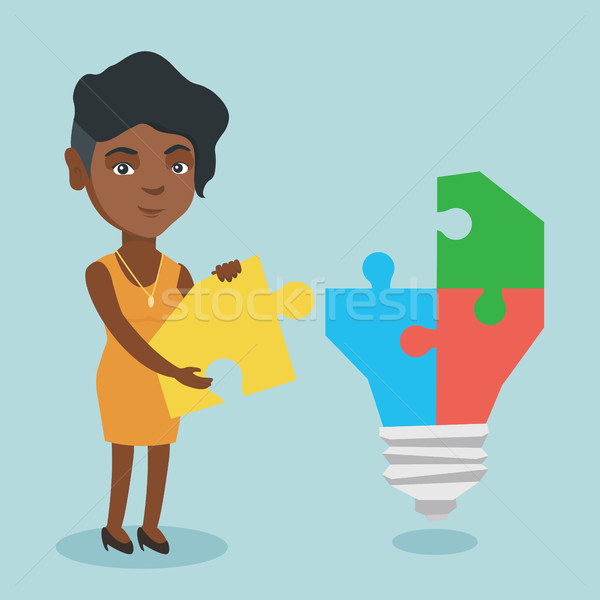 Business woman completing lightbulb made of puzzle Stock photo © RAStudio