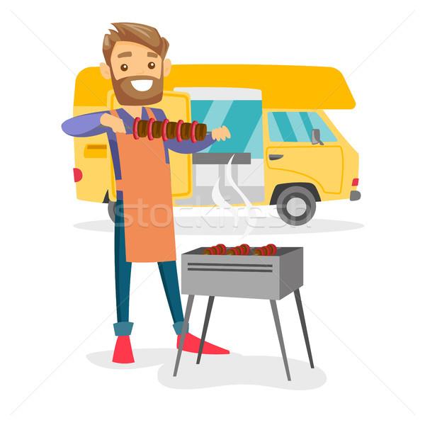 Young man barbecuing meat in front of camper van. Stock photo © RAStudio