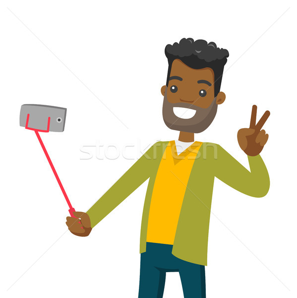 A black man making selfie on his cellphone with a selfie stick. Stock photo © RAStudio