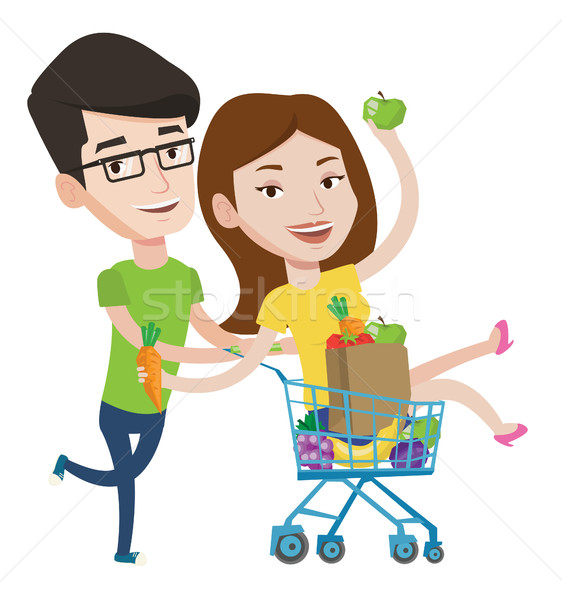 Couple of friends riding in shopping trolley. Stock photo © RAStudio