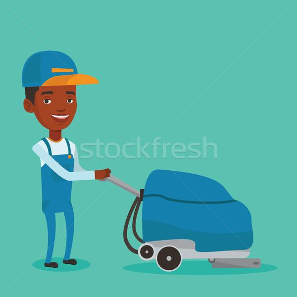 Male worker cleaning store floor with machine. Stock photo © RAStudio