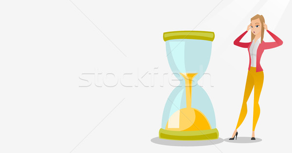 Desperate business woman looking at hourglass. Stock photo © RAStudio