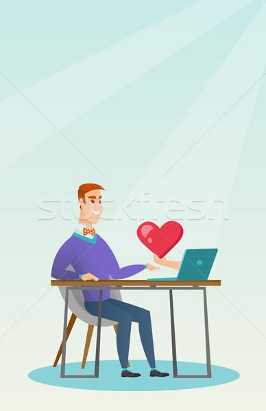 Young man using a laptop online dating. Stock photo © RAStudio