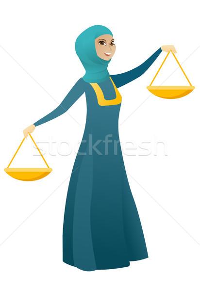 Muslim business woman holding balance scale. Stock photo © RAStudio