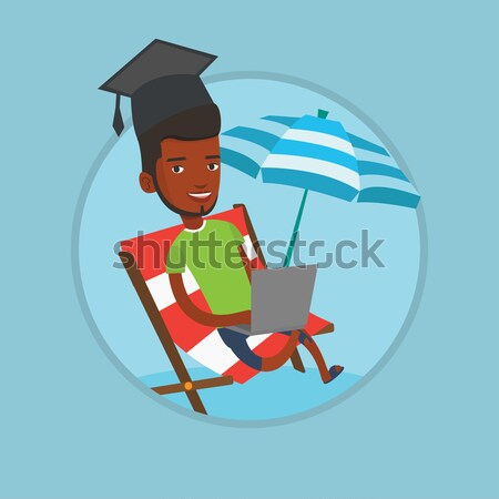 Graduate lying in chaise lounge with a laptop. Stock photo © RAStudio