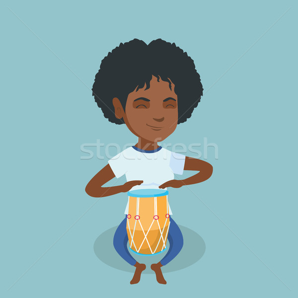 Stock photo: Young african woman playing the ethnic drum.