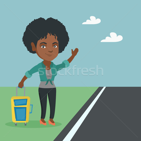 Young african woman with a suitcase hitchhiking. Stock photo © RAStudio