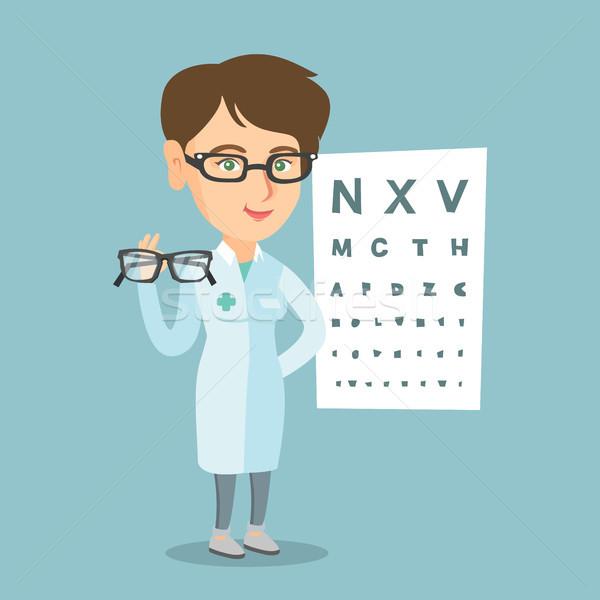 Caucasian ophthalmologist holding eyeglasses. Stock photo © RAStudio