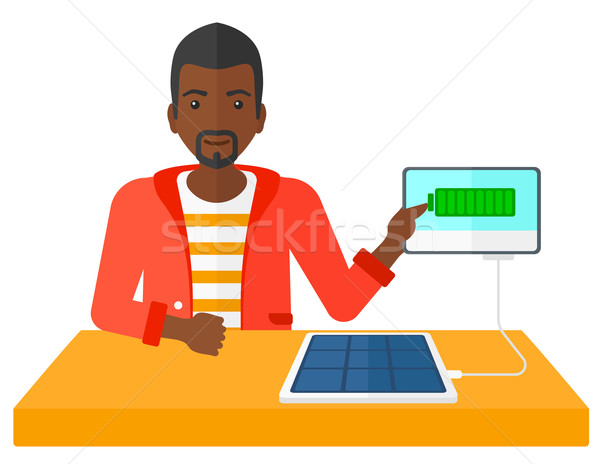 Solar panel charging tablet cumputer. Stock photo © RAStudio