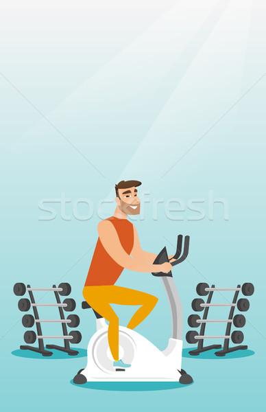 Fiatalember lovaglás mozdulatlan bicikli kaukázusi hipszter Stock fotó © RAStudio