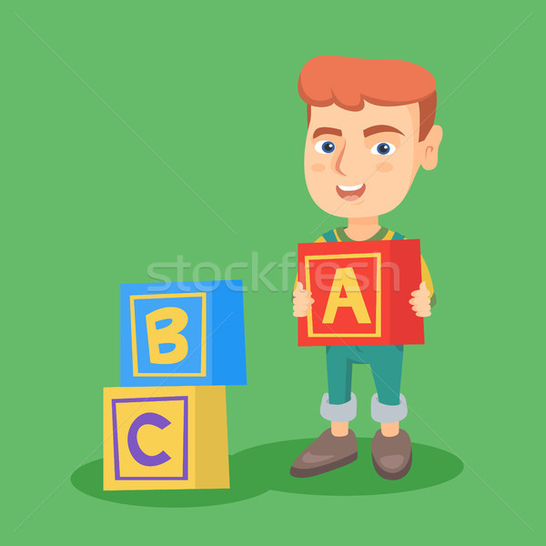 Stock photo: Smiling caucasian boy playing with alphabet cubes.