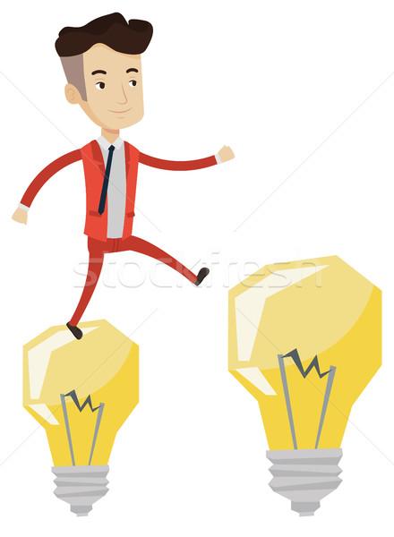 Businessman jumping on light bulbs. Stock photo © RAStudio