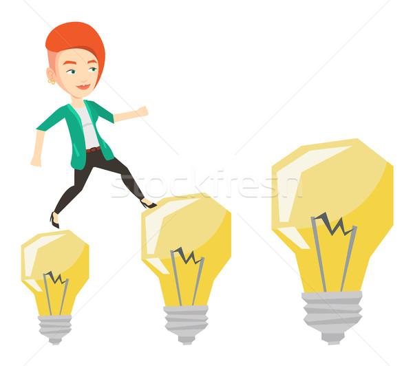 Business woman jumping on light bulbs. Stock photo © RAStudio