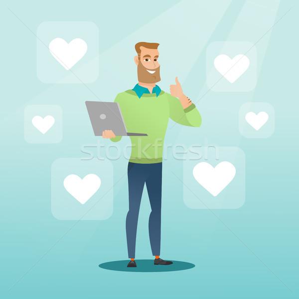 Man with laptop and heart icons. Stock photo © RAStudio
