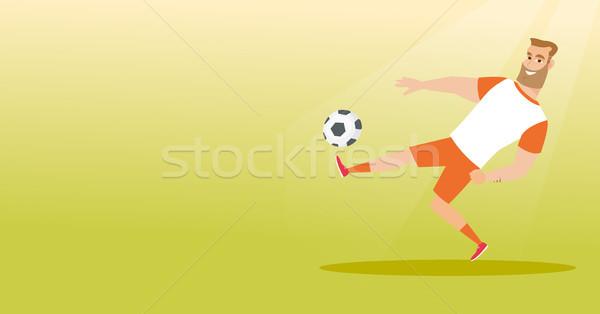 Young caucasian soccer player kicking a ball. Stock photo © RAStudio