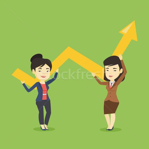 Two business women holding growth graph. Stock photo © RAStudio