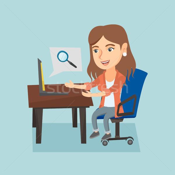 Caucasian woman searching information on a laptop. Stock photo © RAStudio