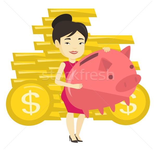 Business woman holding big piggy bank. Stock photo © RAStudio