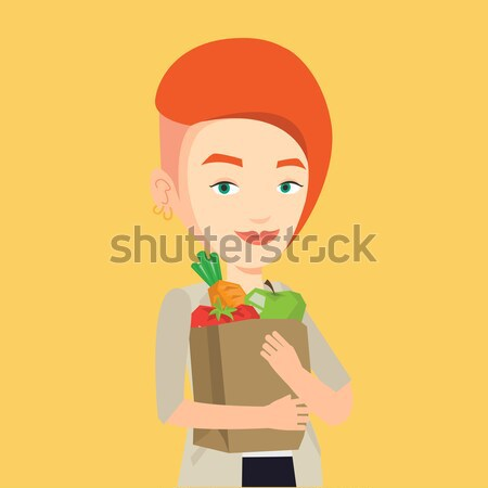 Happy woman holding grocery shopping bag. Stock photo © RAStudio