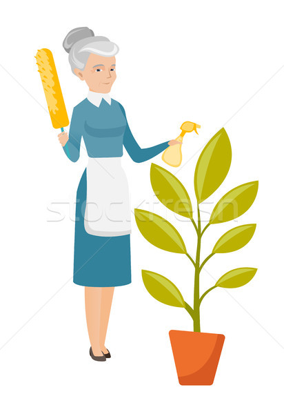 Caucasian housemaid watering flower with spray. Stock photo © RAStudio