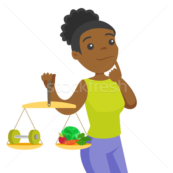 African-american woman weighing food and dumbbell. Stock photo © RAStudio