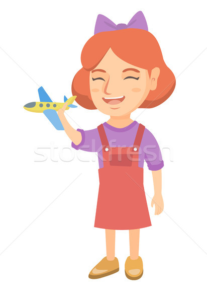 Caucasian cheerful girl playing with toy airplane. Stock photo © RAStudio