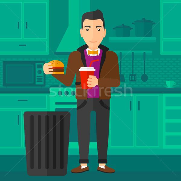 Férfi dob egészségtelen étel áll konyha szemét Stock fotó © RAStudio