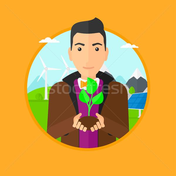 Man holding green small plant. Stock photo © RAStudio