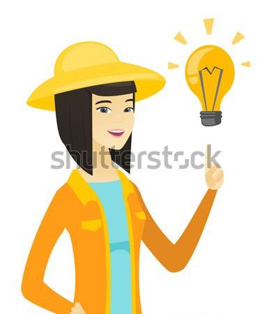 Farmer pointing at bright idea light bulb. Stock photo © RAStudio