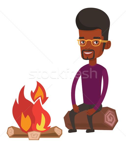 Man sitting on log near campfire in the camping. Stock photo © RAStudio