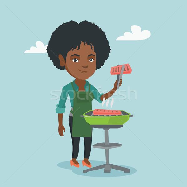 Afryki kobieta gotowania stek grill wesoły Zdjęcia stock © RAStudio