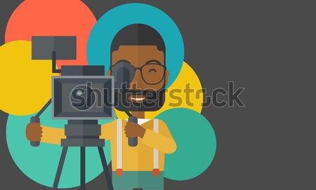 African cameraman with movie camera on tripod. Stock photo © RAStudio