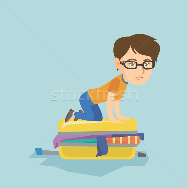 Young caucasian woman trying to close suitcase. Stock photo © RAStudio