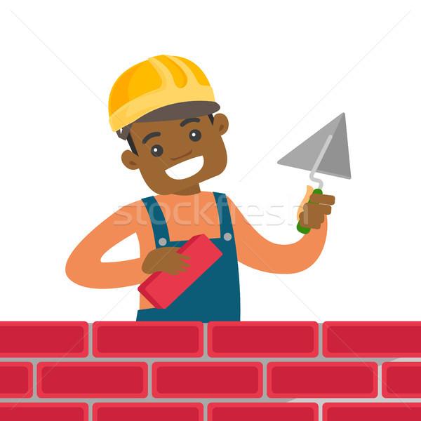 African-american bricklayer building a brick wall. Stock photo © RAStudio