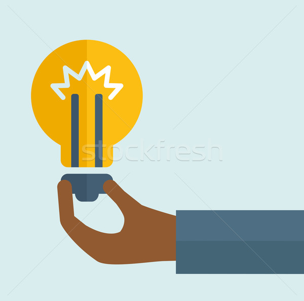 Stock photo: Black hand holding a bulb.