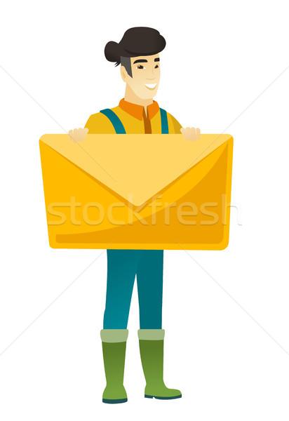 Smiling farmer holding a big envelope. Stock photo © RAStudio